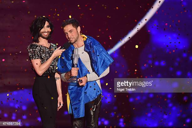 Conchita Wurst hands over the trophy to Mans Zelmerloew of Sweden after winning the final of the Eurovision Song Contest 2015 on May 23, 2015 in...