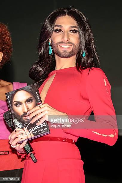Conchita Wurst poses with the book 'Conchita Wurst Maine Geschichte' 'Conchita Wurst My History' at the ViennaSphere at the Moll de la Fusta on March...