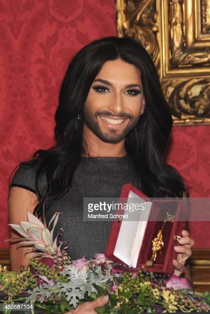 Conchita Wurst receives 'Goldenen Rathausmann' from Viennas Major Michael Haeupl at City Hall on September 17 2014 in Vienna Austria