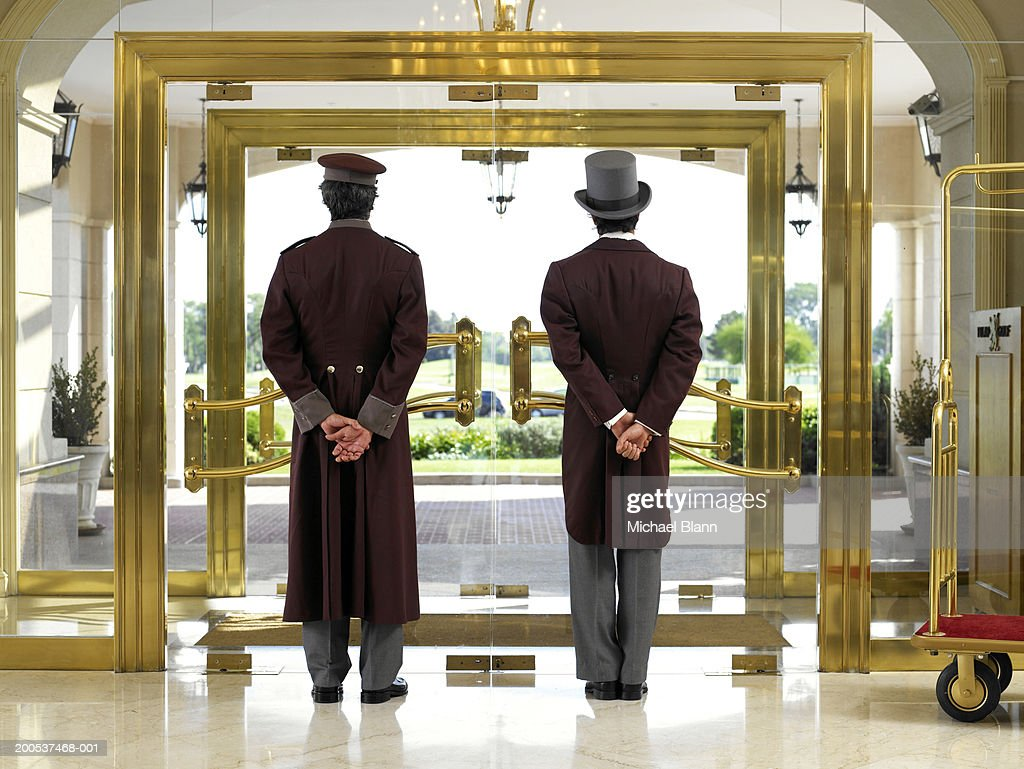 Concierge and bellboy standing at hotel entrance, rear view : Stock Photo