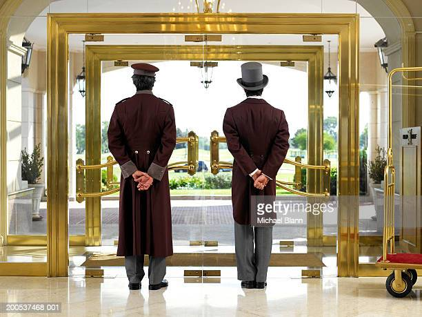 concierge and bellboy standing at hotel entrance, rear view - hotel stock-fotos und bilder