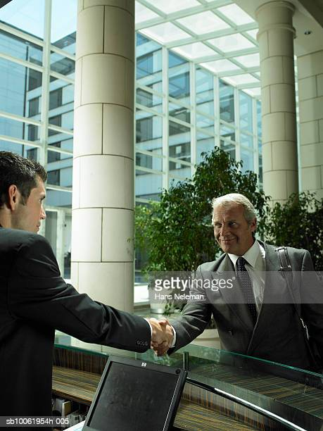 Concierge and mature businessman shaking hands at hotel lobby