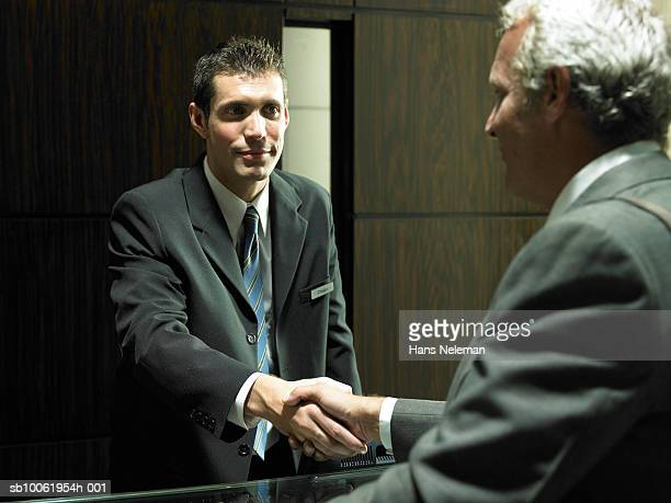 Concierge and mature businessman shaking hands