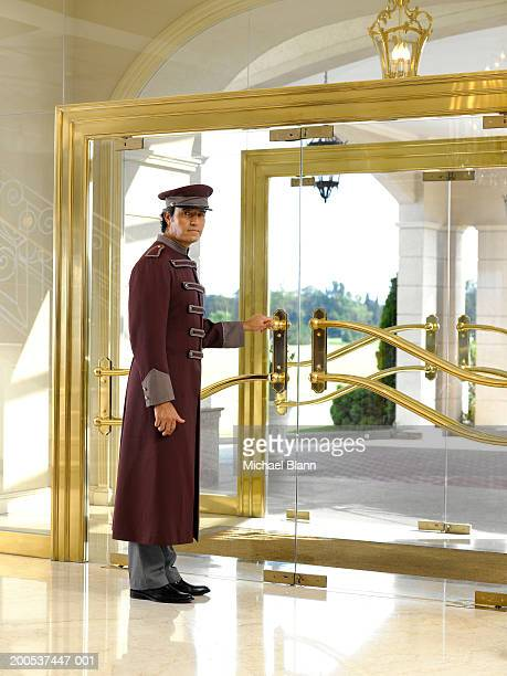 Concierge holding door in hotel foyer, portrait