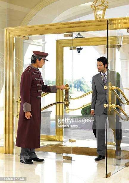 Concierge holding door open for businessman