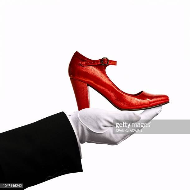 Concierge holding red shoe