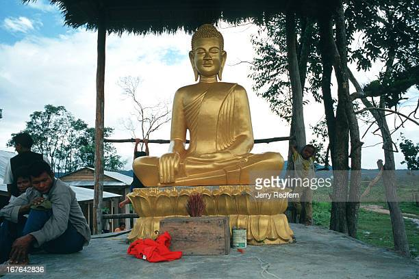 A concrete and gold painted Buddha statue donated to Veal Thom by King Sihanouk is one of the very few landmarks in the tiny Veal Thom village Deep...