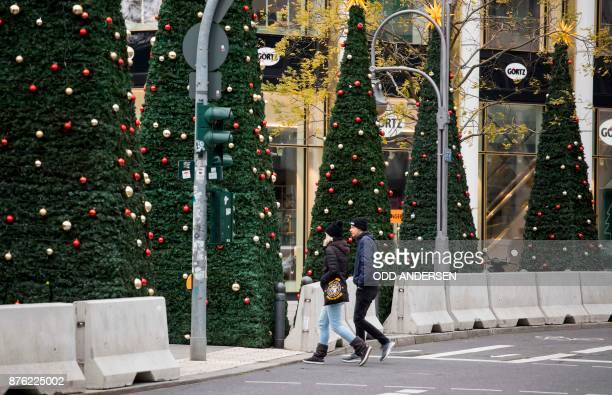 Concrete barriers are seen surrounding the Christmas market as people cross the street at Breitscheidplatz in central Berlin on November 19 2017...