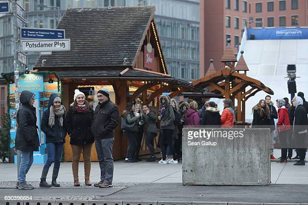 A concrete block placed there as a security barrier stand near visitors at a Christmas market at Potsdamer Platz that has reopened following the...