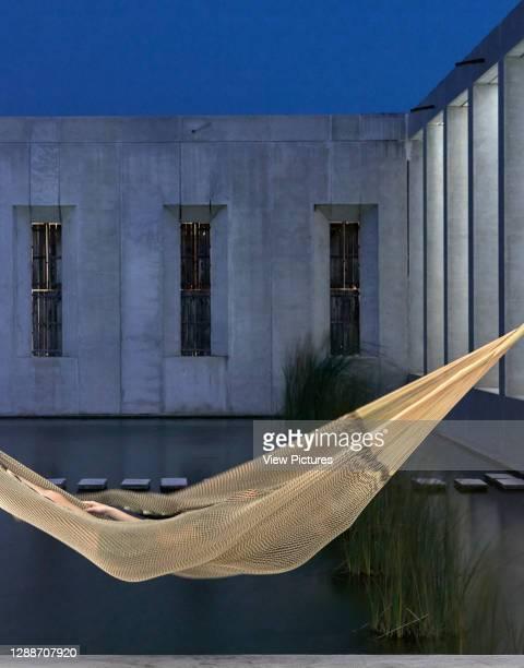 Concrete facade of grand hall with hammock. Plantel Matilde, Yucatan, Mexico. Architect: Javier Marín and Arcadio Marín, 2020.