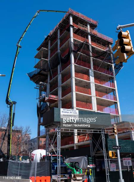 Concrete from a pumping truck is spread by construction workers on a 15-story residential condominium building in Cobble Hill, Brooklyn, New York...