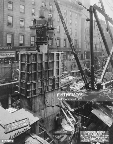 Concrete is poured into one of the massive columns supporting the superstructure of the Woolworth Building in New York City 10th August 1910 The view...