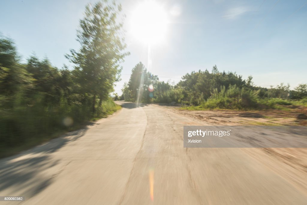 Concrete road under blue sky with clouds in motion blur with plants in sides : Photo
