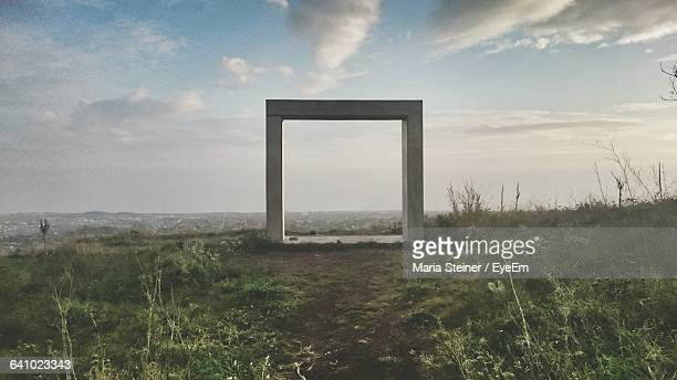 Concrete Square On Grassy Field Against Sky