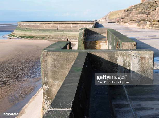 concrete stairs on seawall in blackpool with the beach at low tide in sunlight - blackpool beach stock pictures, royalty-free photos & images