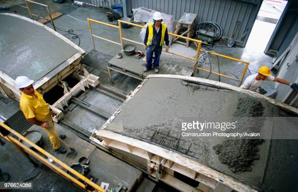 A concrete tunnel lining segment emerges in its steel mould from the concrete pouring chamber before hand finishing for steam curing Spanish High...