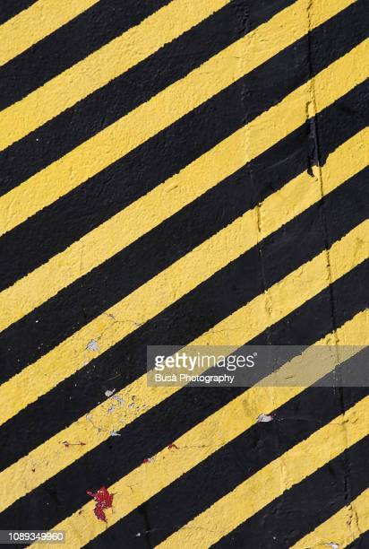 concrete wall painted with yellow and black stripes, usually used in construction sites with the meaning: do not enter the area / caution - torto imagens e fotografias de stock