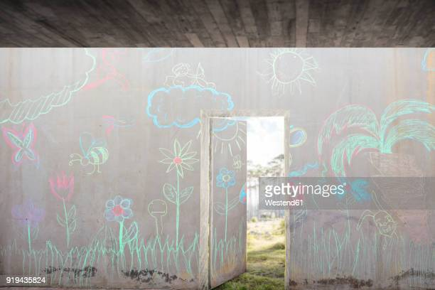 Concrete wall with colourful chalk drawings and open door