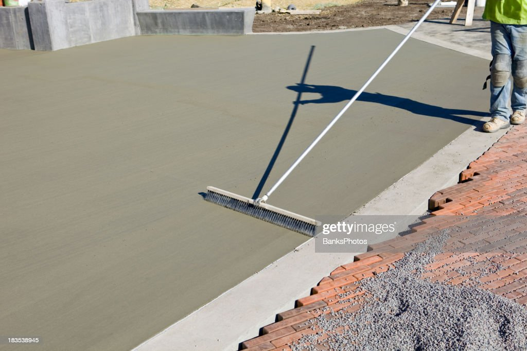 Concrete Worker Brushing Texture Into A New Patio Slab : Stock Photo