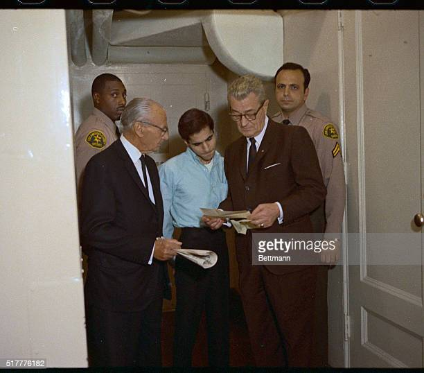 Condemned assassin Sirhan B Sirhan listens intently to his Chief Defense Attorney Grant B Cooper as codefense attorney Russell E Parsons looks on...