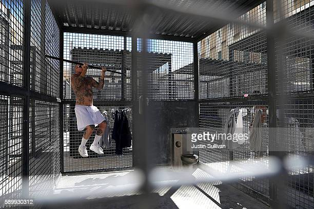 A condemned inmate does pullups while working out in yard outside of San Quentin State Prison's death row adjustment center on August 15 2016 in San...