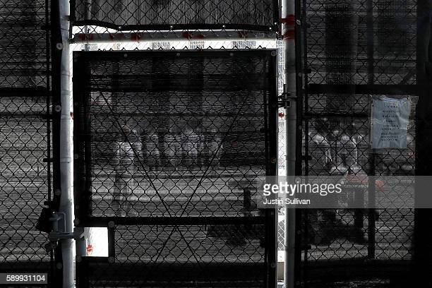 Condemned inmates are seen through black mesh as they stand in an exercise yard at San Quentin State Prison's death row on August 15 2016 in San...