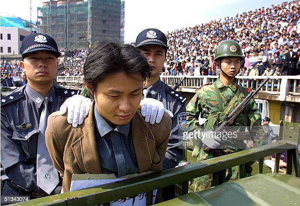 Condemned prisoner Liu Tianlong who was sentenced to death for robbery and murder under guard as he is paraded in front of thousands of spectators...