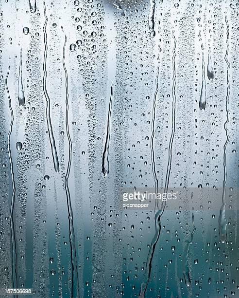 Condensation runs down a window pane