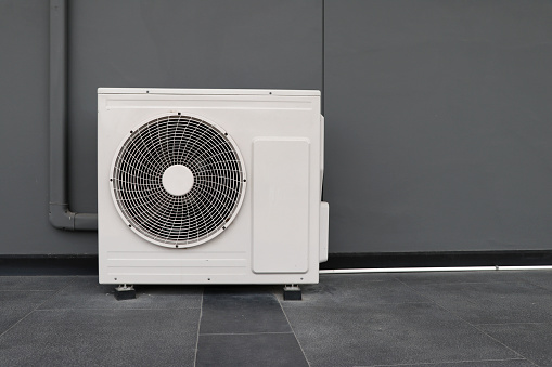 Condensing unit of air conditioning systems. Condensing unit installed on the gray wall. 1160239808
