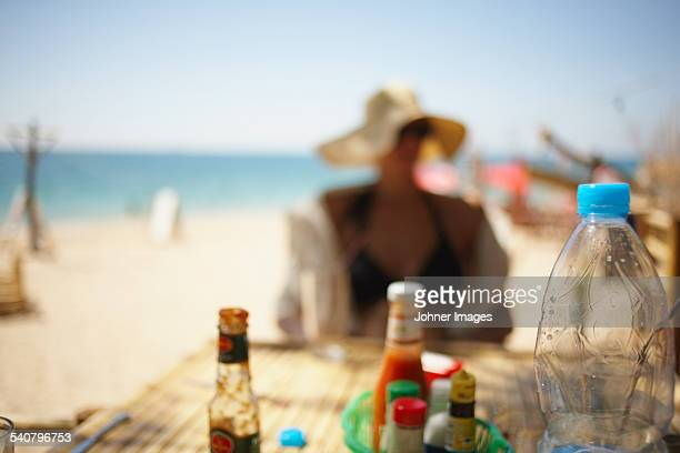 Condiments on table, woman on background