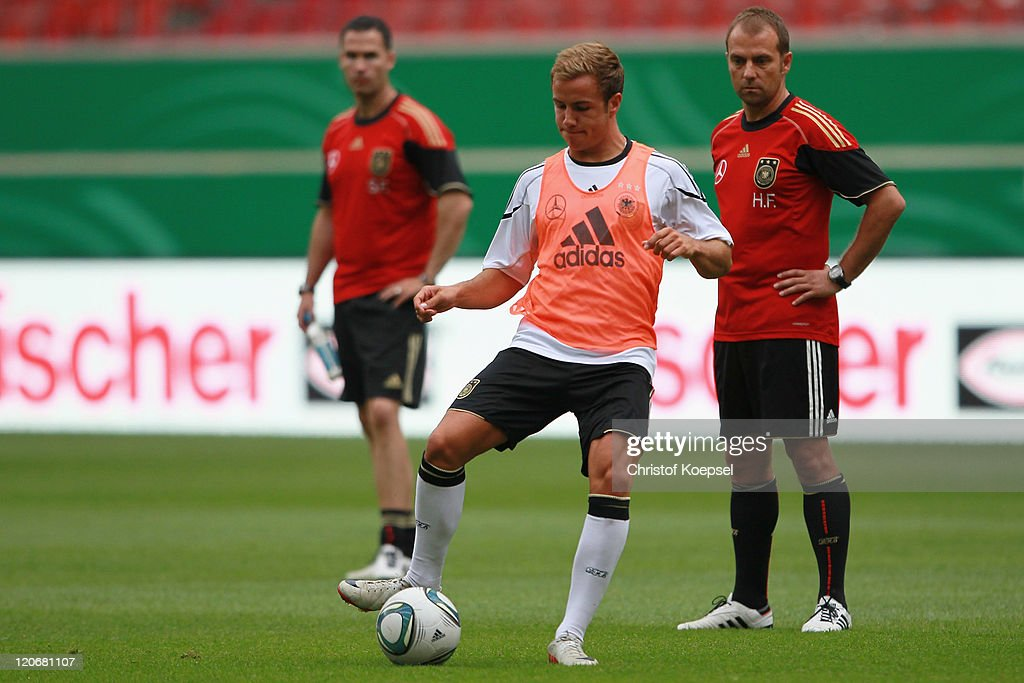 Condition coach Shad Forsythe (L) and assistant coach Hansi Flick (R) watch Mario Goetze (C) shooting a ball during a training session of the German National football team at Mercedes-Benz Arena on August 8, 2011 in Stuttgart, Germany. Germany will play a friendly match against Brazil at Mercedes-Benz Arena on August 10, 2011 in Stuttgart, Germany.