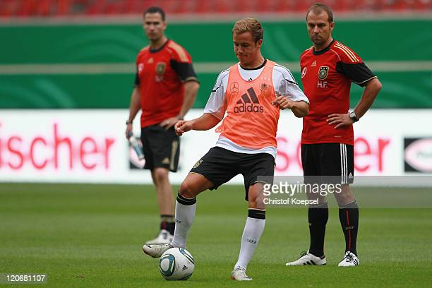 Condition coach Shad Forsythe and assistant coach Hansi Flick watch Mario Goetze shooting a ball during a training session of the German National...