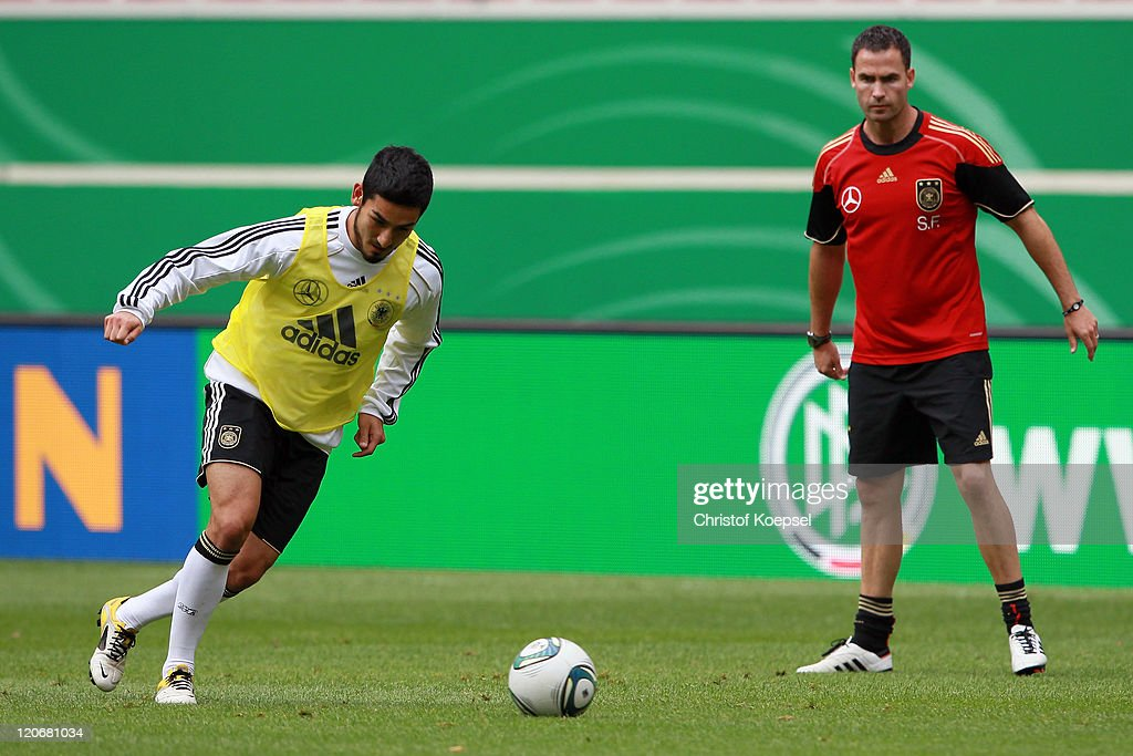 Condition coach Shad Forsythe (R) watches at Ilkay Guendogan shooting a ball during a training session of the German National football team at Mercedes-Benz Arena on August 8, 2011 in Stuttgart, Germany. Germany will play a friendly match against Brazil at Mercedes-Benz Arena on August 10, 2011 in Stuttgart, Germany.