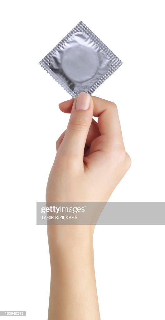 condom in female hand isolated on a white background : Stock Photo