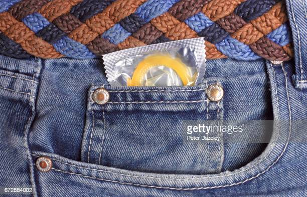 condom in jeans pocket close up - geschlechtskrankheit stock-fotos und bilder
