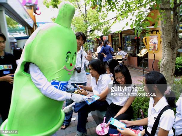 A condom mascot offers leaflets to Thai teenagers 24 August 2001 during a promotional campaign by condom manufacturer 'Durex' to educate Thai youths...