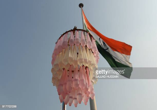 Condoms filled with water hang from a display during an event to mark International Condom Day in New Delhi on February 13 2018 The event was...