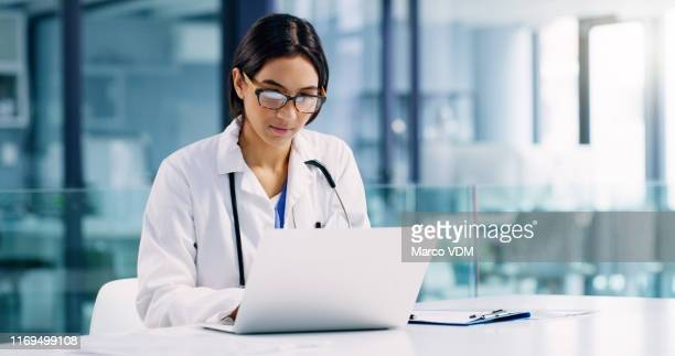 conducting further research to improve her healthcare services - computer foto e immagini stock