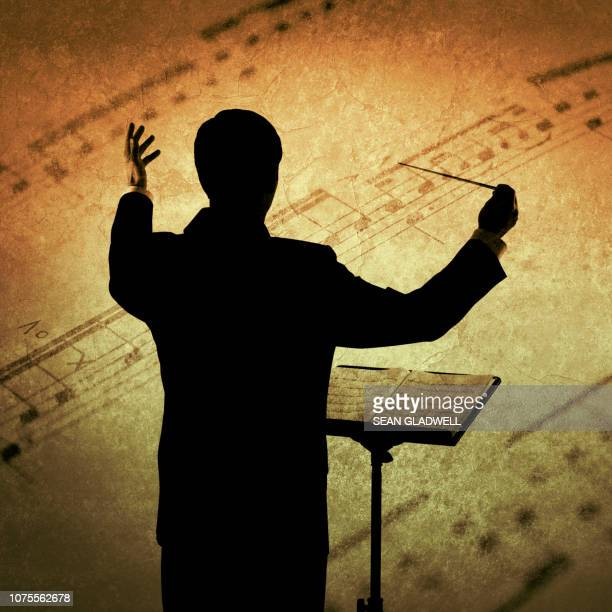 conductor and sheet music - musical conductor stock pictures, royalty-free photos & images