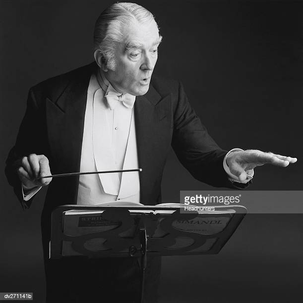 conductor at stand waving hands - headhunters stock pictures, royalty-free photos & images