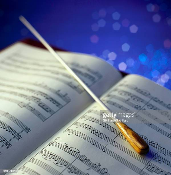 conductor baton and sheet music - conductor's baton stock photos and pictures