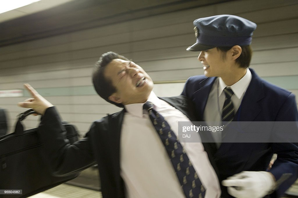 Conductor carrying drunk businessman at platform, blurred motion : Stock Photo
