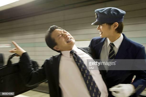 Conductor carrying drunk businessman at platform, blurred motion