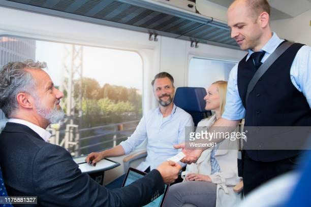 conductor checking tickets of passengers in a train - bahnreisender stock-fotos und bilder