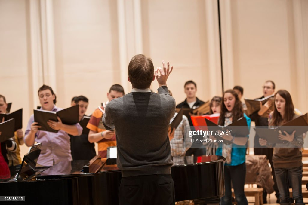 Conductor directing choir on stage : Stock Photo