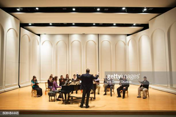 conductor directing choir on stage - concert hall stock pictures, royalty-free photos & images