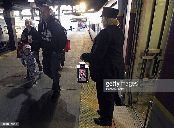 Conductor Karen Fisher welcomes children and their families onto the Polar Express leaving South Station The Massachusetts Bay Commuter Railroad...