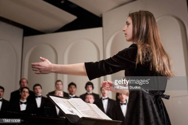 conductor leading choir on stage - musical conductor stock pictures, royalty-free photos & images