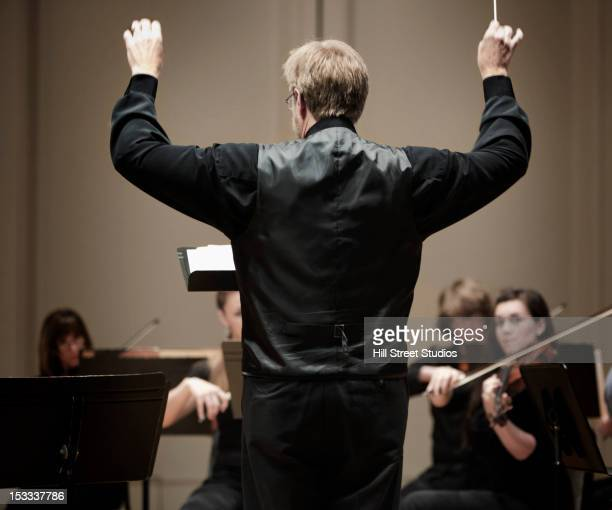 conductor leading orchestra - musical conductor stock pictures, royalty-free photos & images