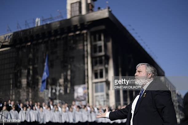 A conductor leads a choir during a rally to commemorate the 200th anniversary of poet and national icon Taras Shevchenko at Independence Square in...
